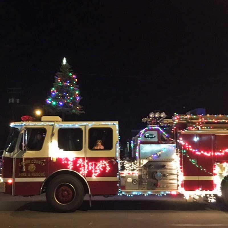 A fire truck is adorned in holiday lights.