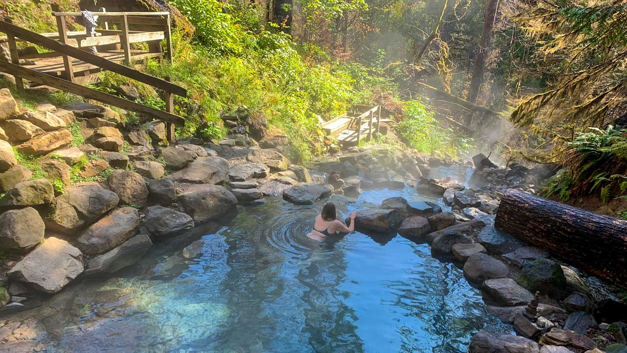 A woman relaxes in a steamy hot spring.
