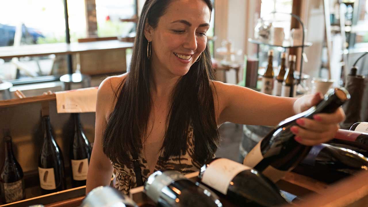Woman picks up wine bottle and admires the label.