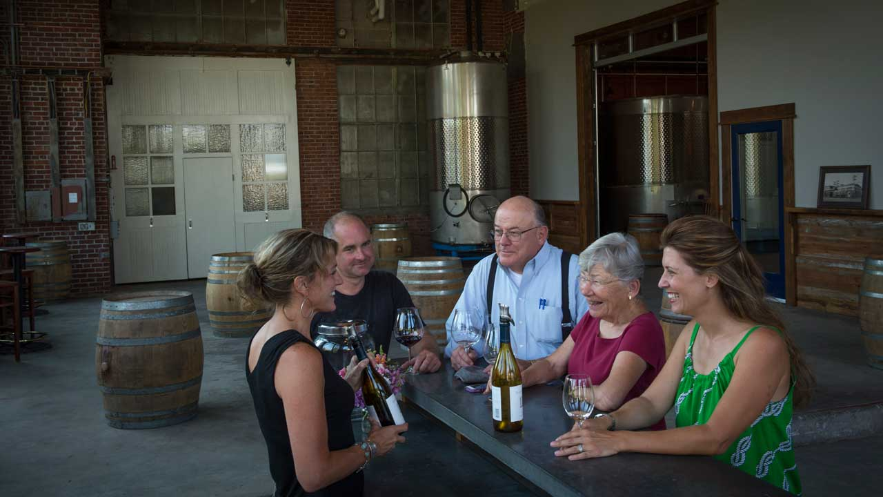 A group of five people laugh as they sip wine in a cozy Oregon tasting room.