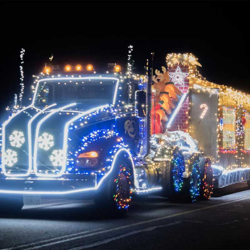 A semi-truck is illuminated in holiday lights in the shapes of snowflakes and stars.