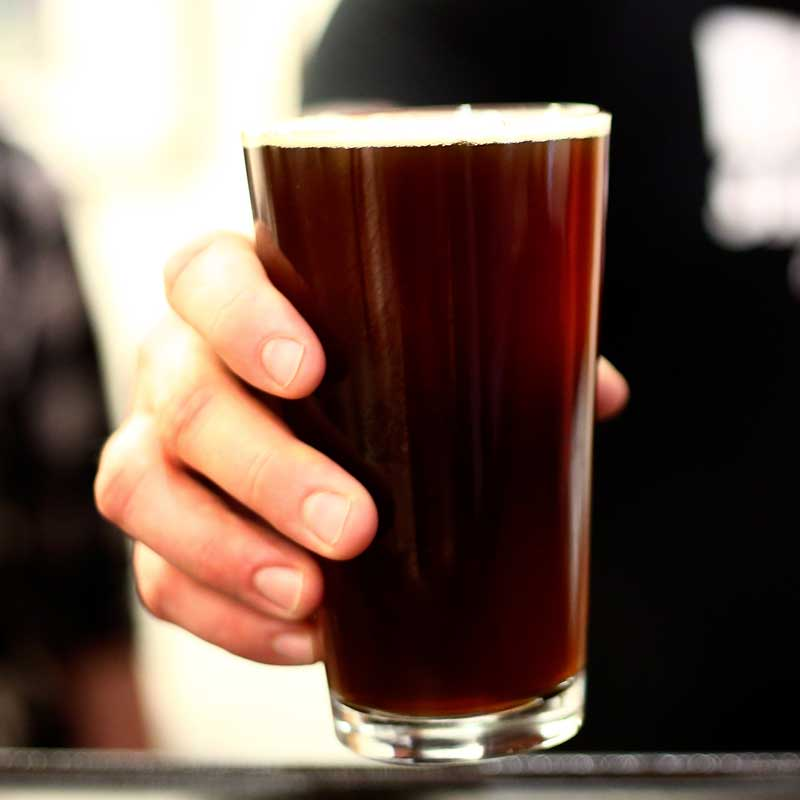 A hand offers a pint of dark winter beer.