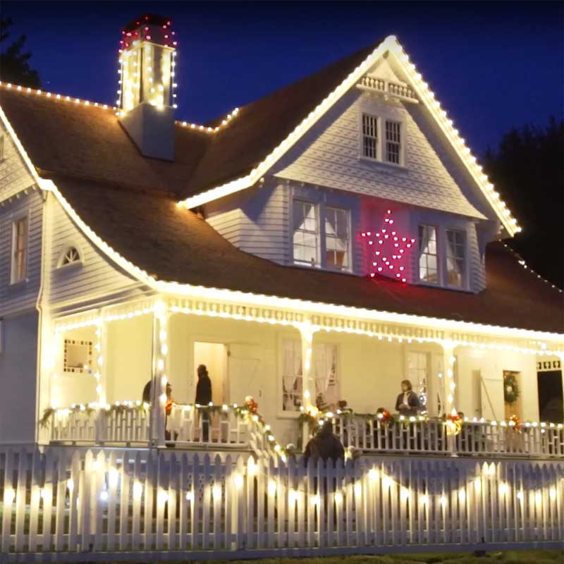 The lightkeeper's house is decoarate with holiday lights, including a red star.