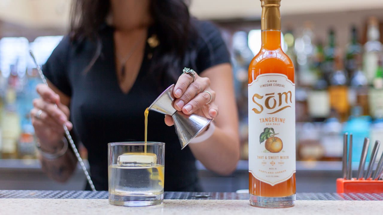A bartender pours a vinegar cordial of tangerine and sea salt.