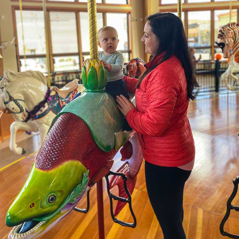 A baby sits on a carousel animal that is shaped like a fish.