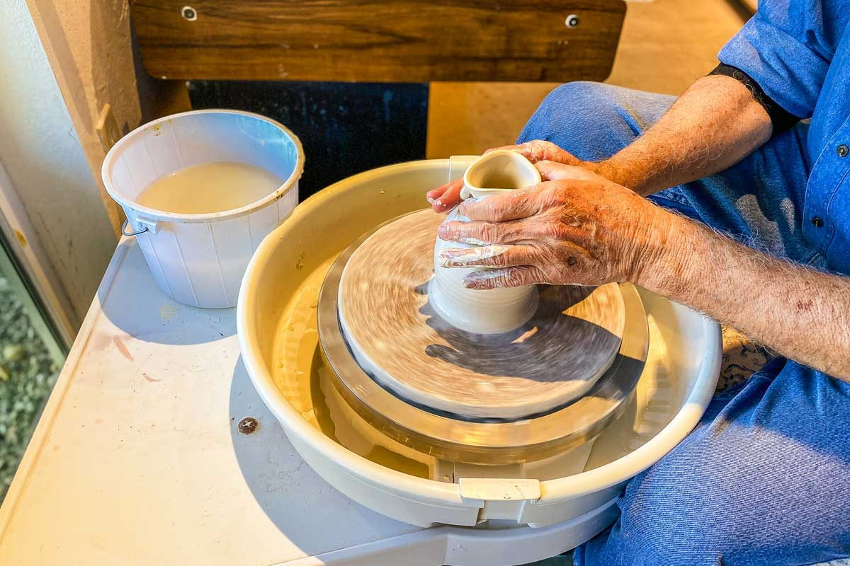 A close-up of Dale shaping clay on a pottery wheel.