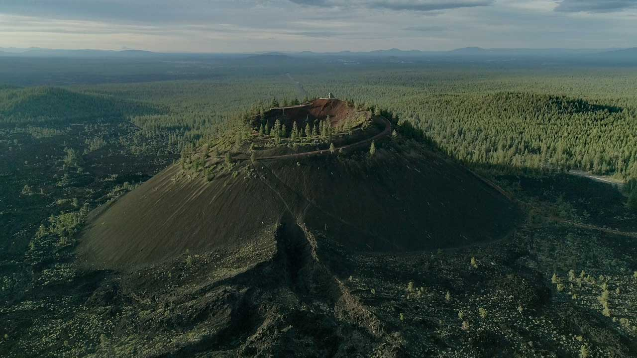 A volcanic butte looms over a forest.