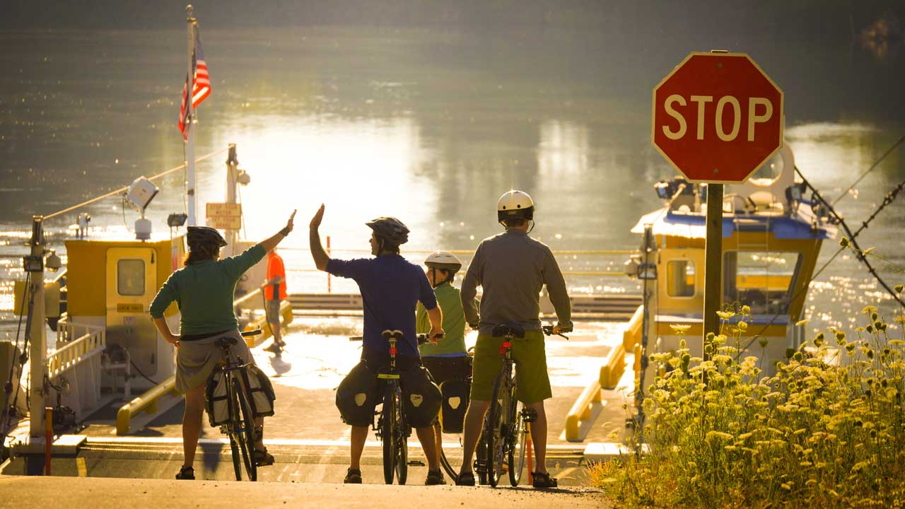 Bicyclists high-five before boarding the ferry.