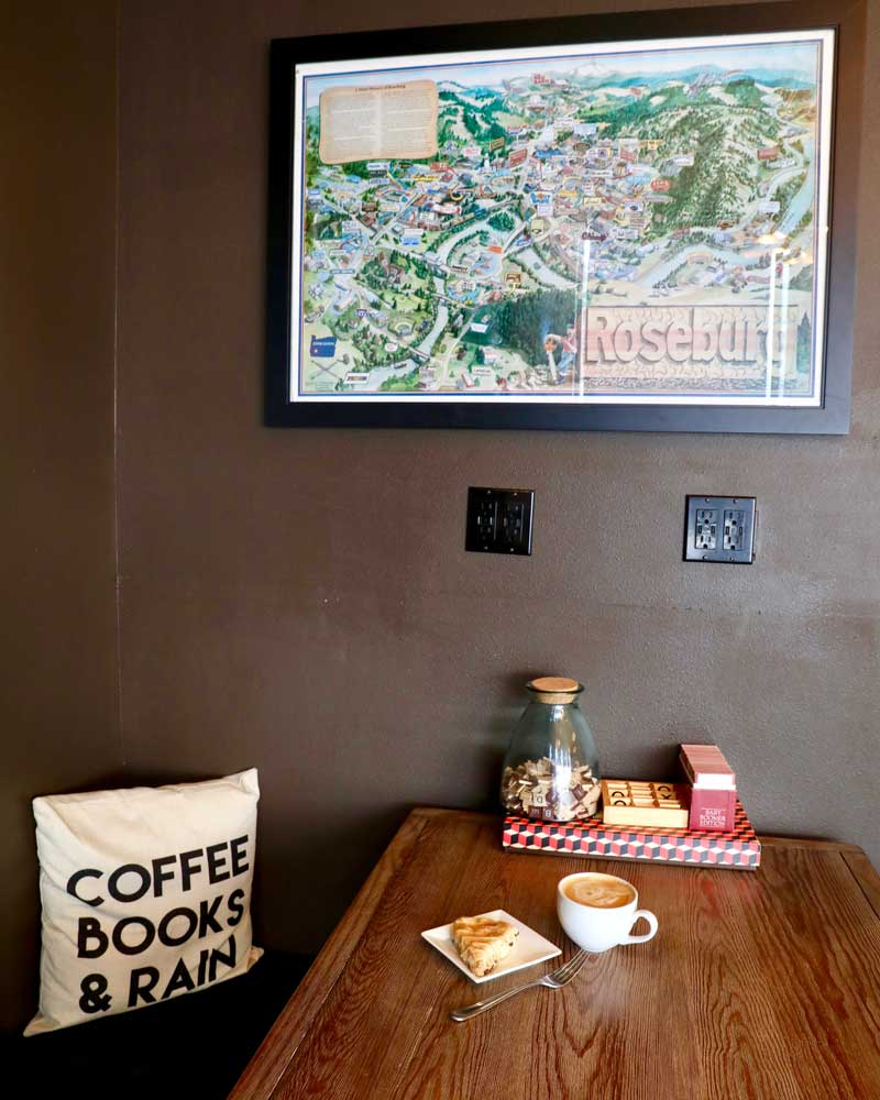 """A pillow says """"coffee, books and rain"""" next to table with coffee."""