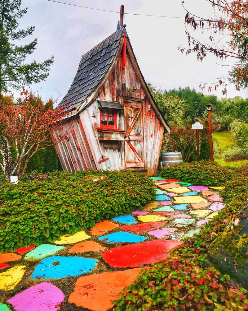 Colorful painted stones line the way to a quirky small building.