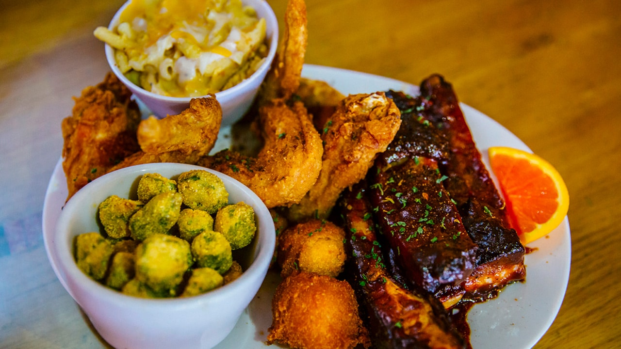 Mac and cheese, chicken wings, ribs, and breaded vegetables on a plate.