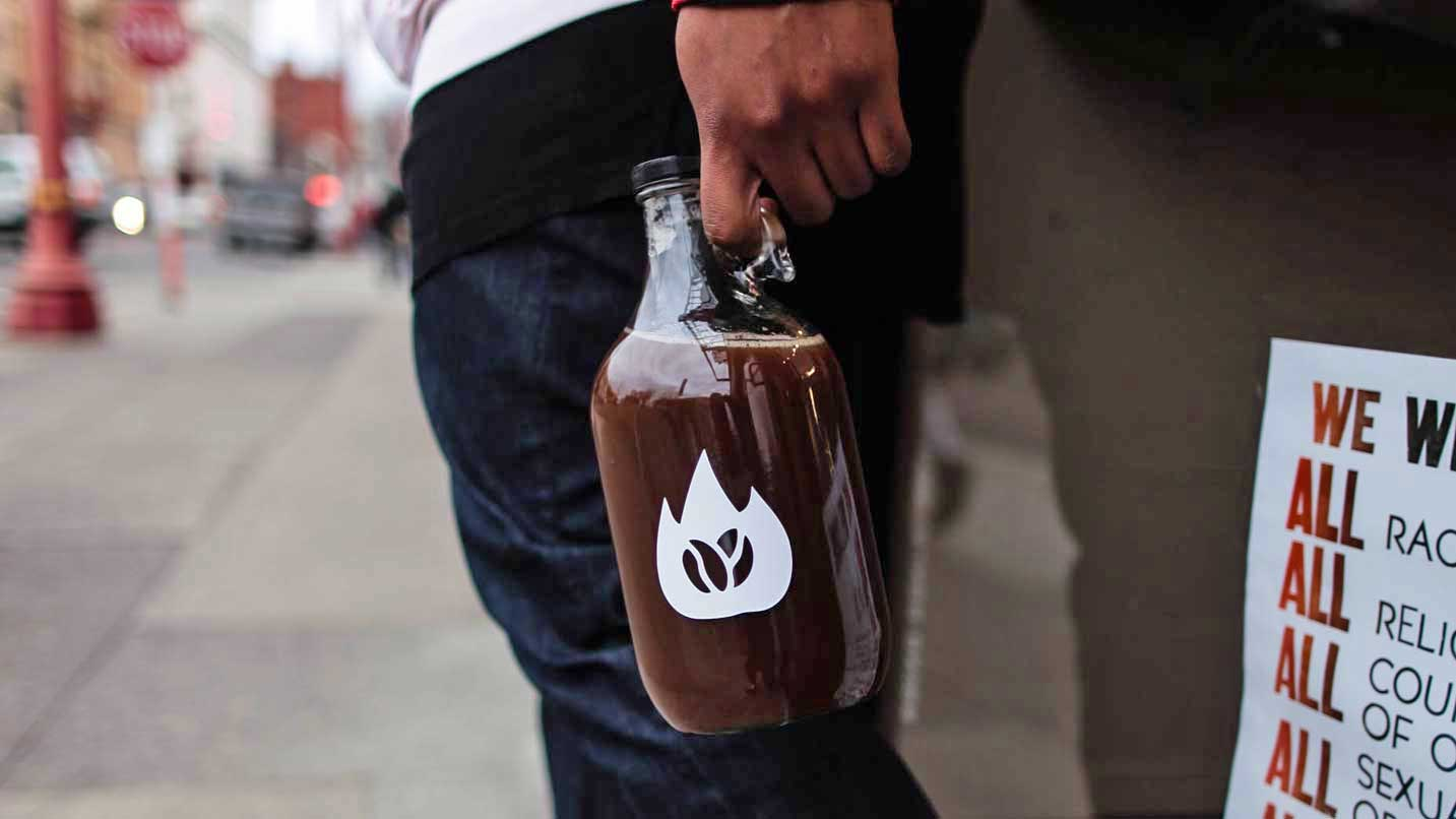 A hand holding a growler of coffee.