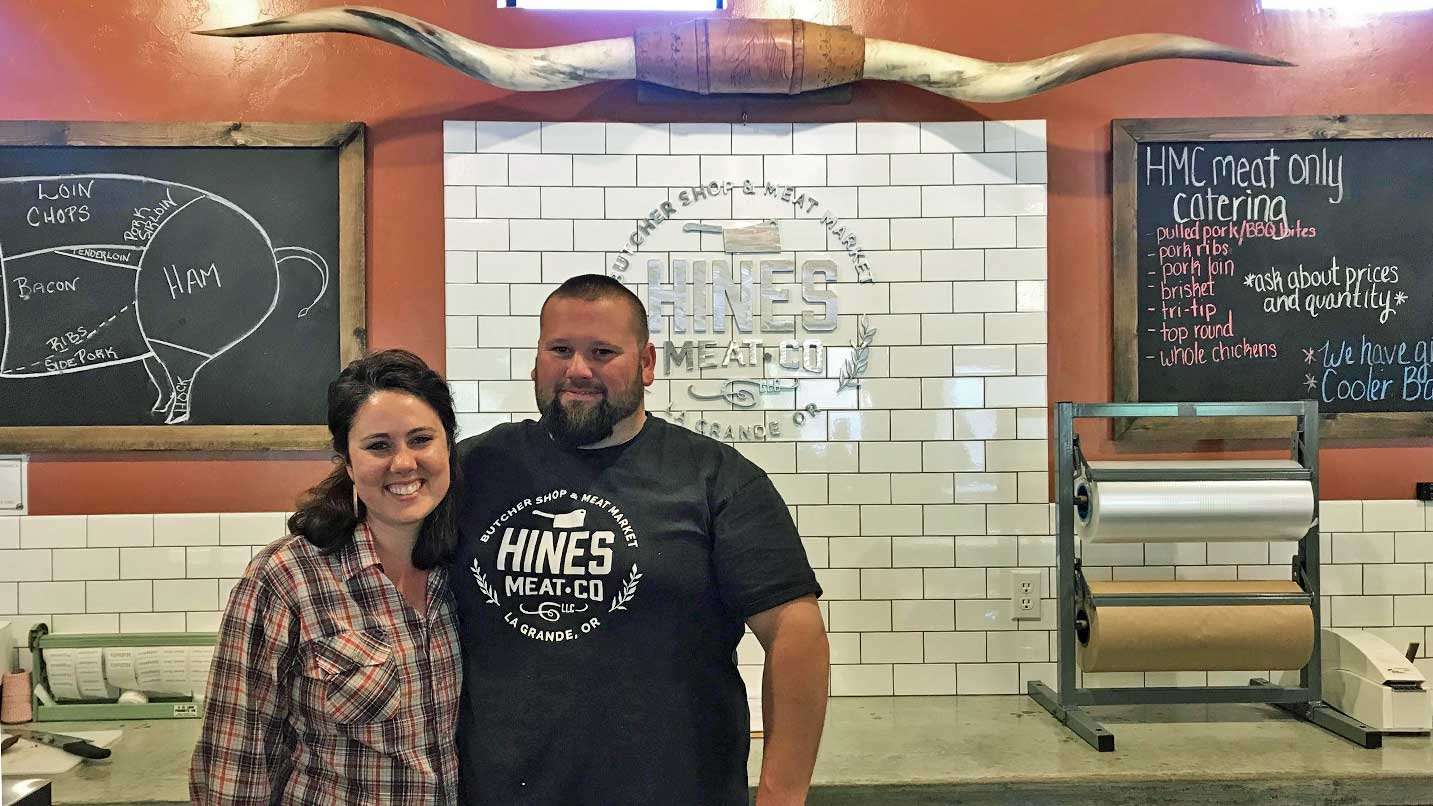 Jake and Paige Hines smile in front of their Hines Meat Co. sign.