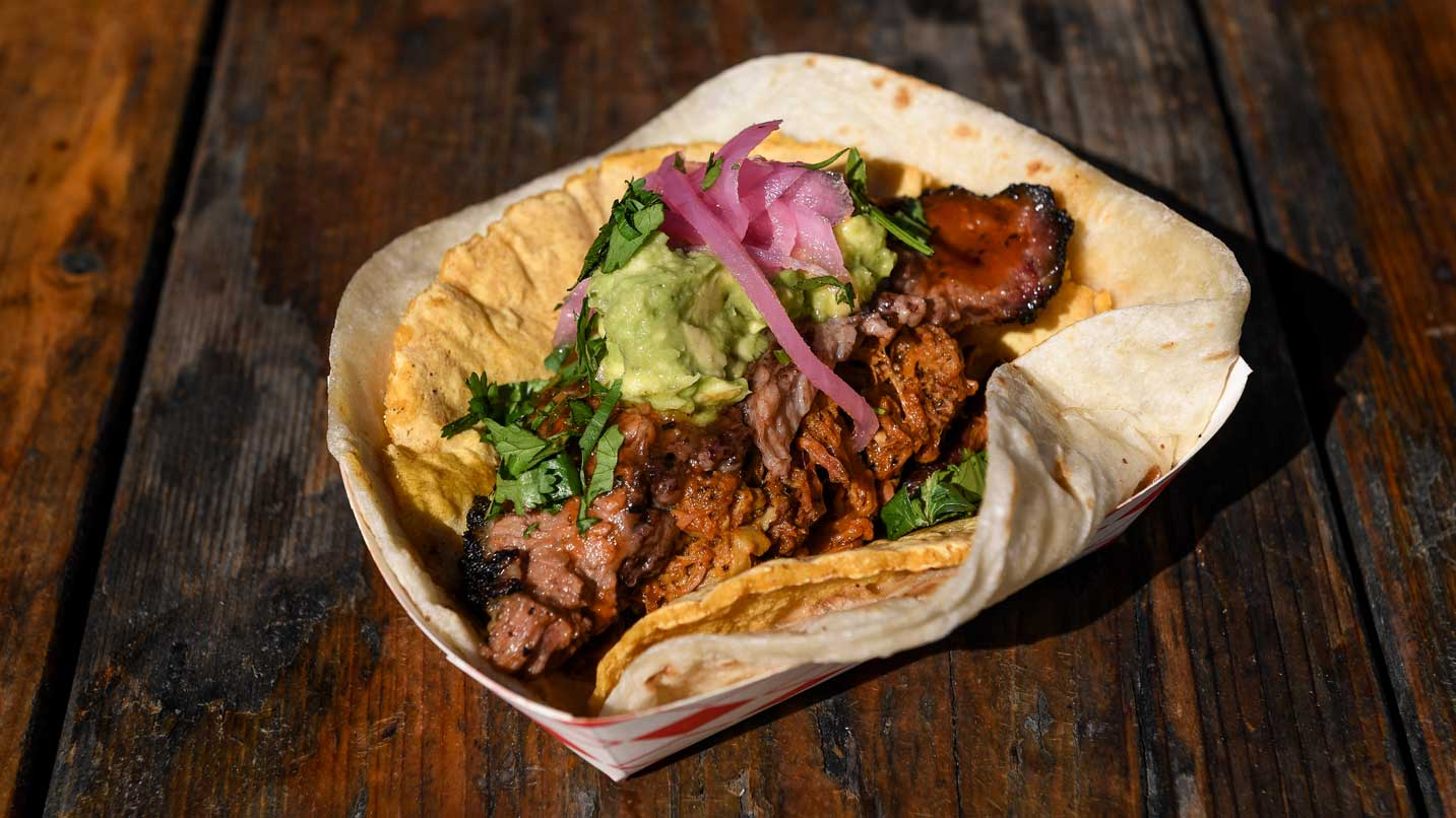 A taco with BBQ meat and guacamole overfills a plate.