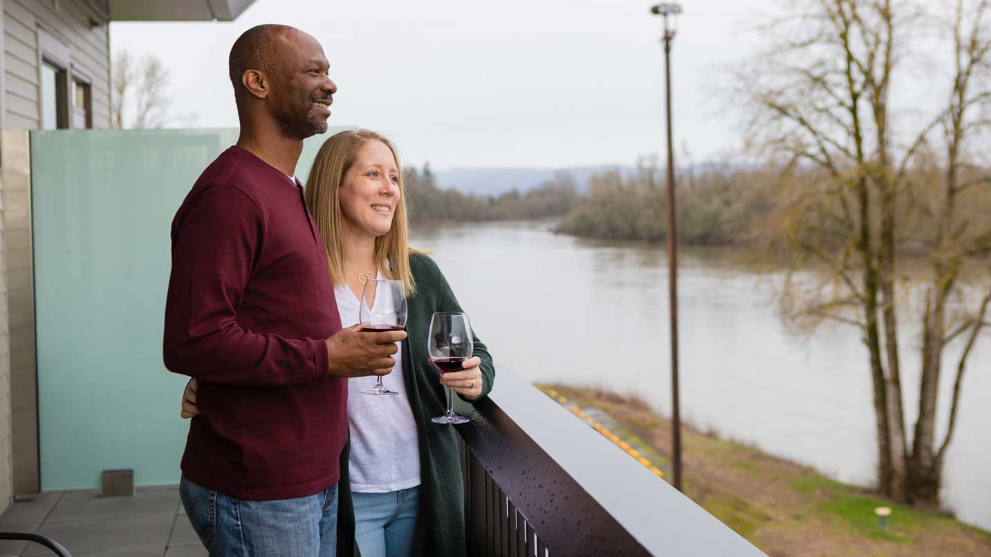 A couple holds glasses of wine while looking out at the river from their deck.