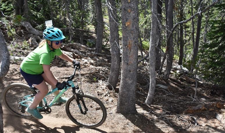 Child biking on a wooded mountain bike trail in Eastern Oregon