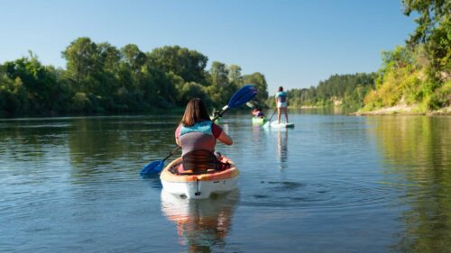 A kayaker paddles behind a stand-up paddleboarder on the Willamette River.