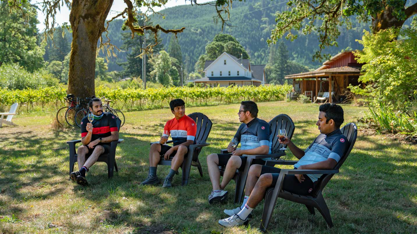 Four cyclists rest in lawn chairs in front of a vineyard with wine glasses in their hands.