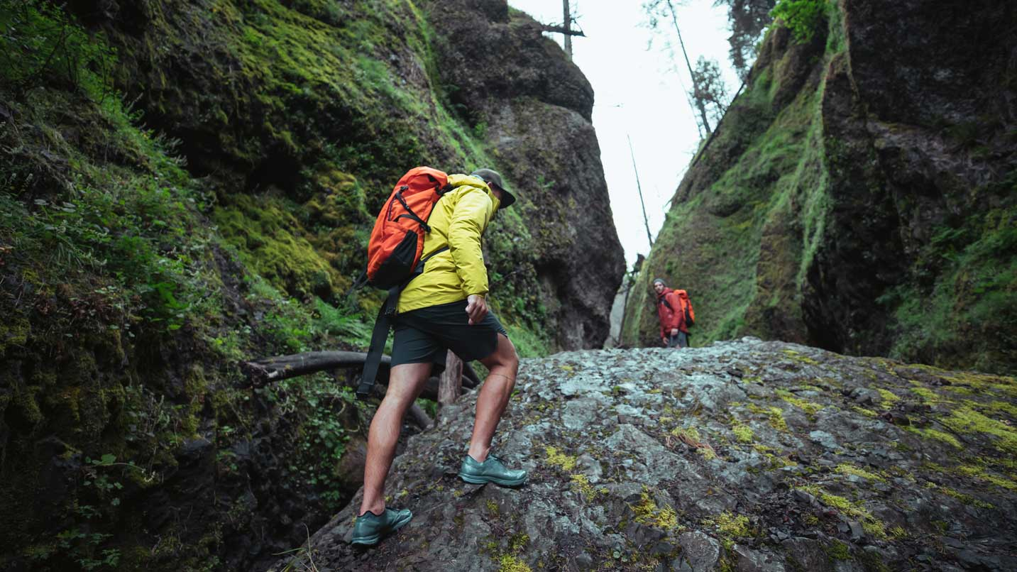Two hikers walk up a rocky path in between mossy boulders.