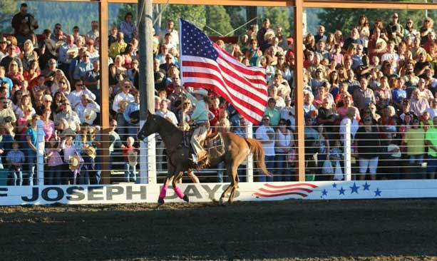 Person on horse carrying American flag