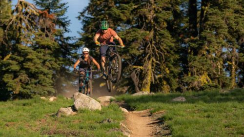 Two mountain bikers get air on a forest trail.