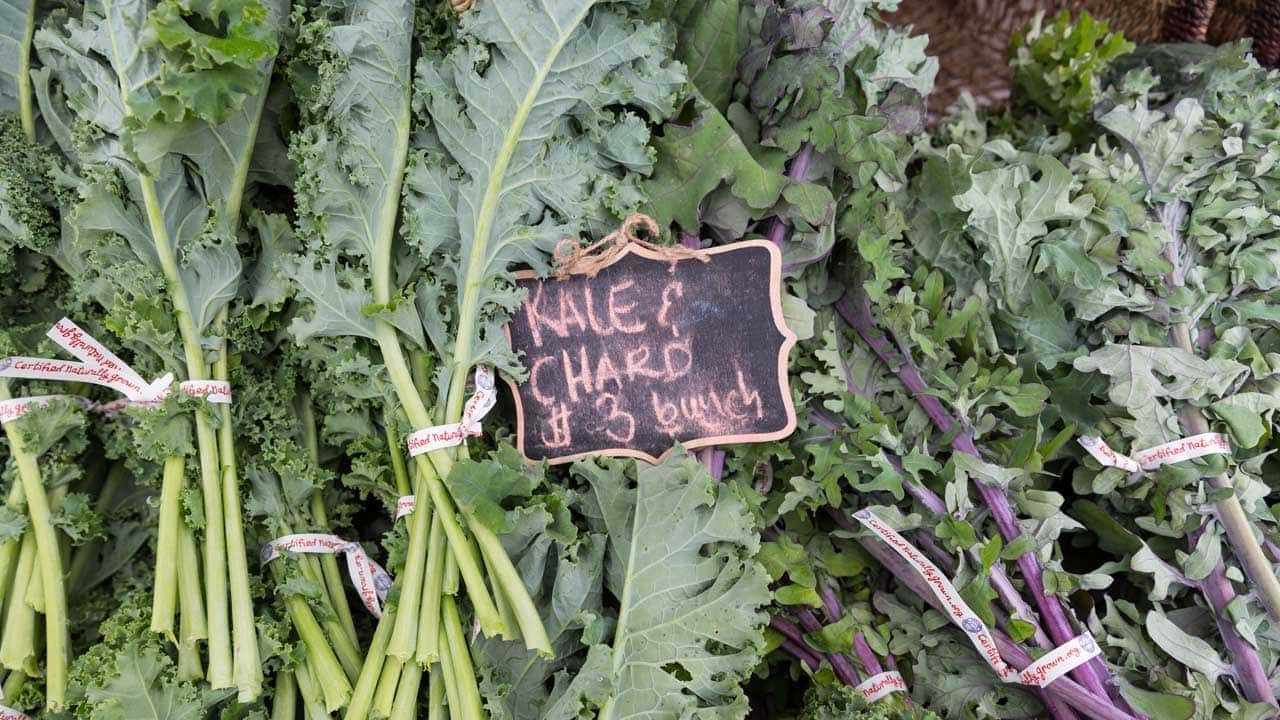 A closeup of kale and chard with a sign saying $3 for a bunch.