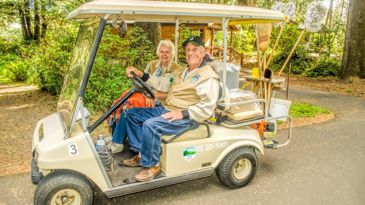 Two elderly people riding in a golf cart collecting trash