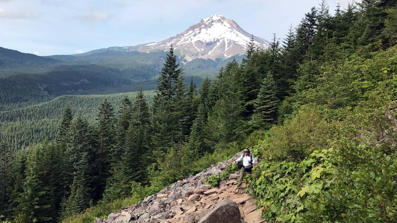 A person hiking on rocks with a view of a mountain from Tom Dick and Harry Mountain
