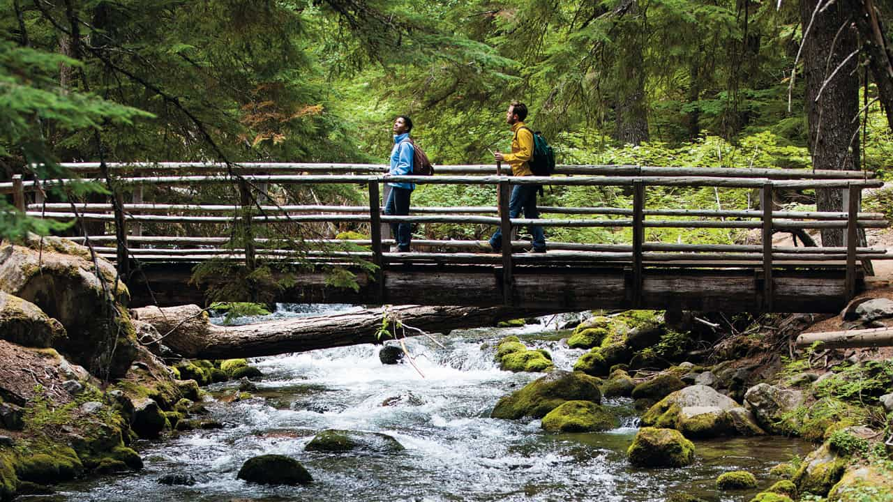 Two people on a bridge on the Tamanawas Falls trail