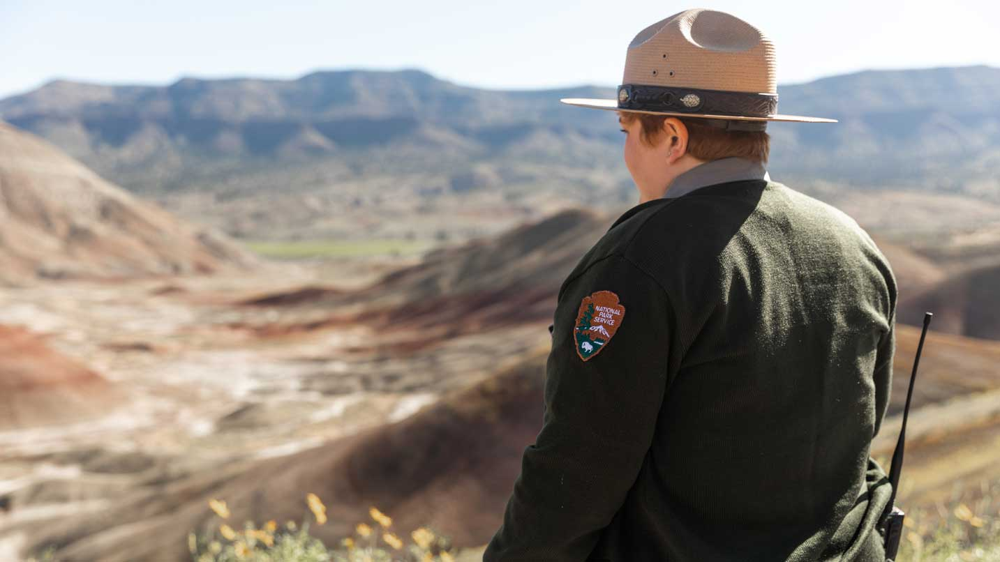 A National Parks ranger looks out at the Painted Hills.