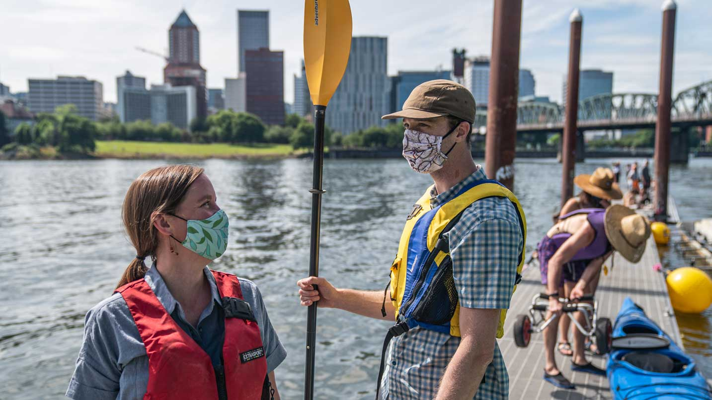 Two people wearing face coverings get ready to paddle on a popular boat ramp.