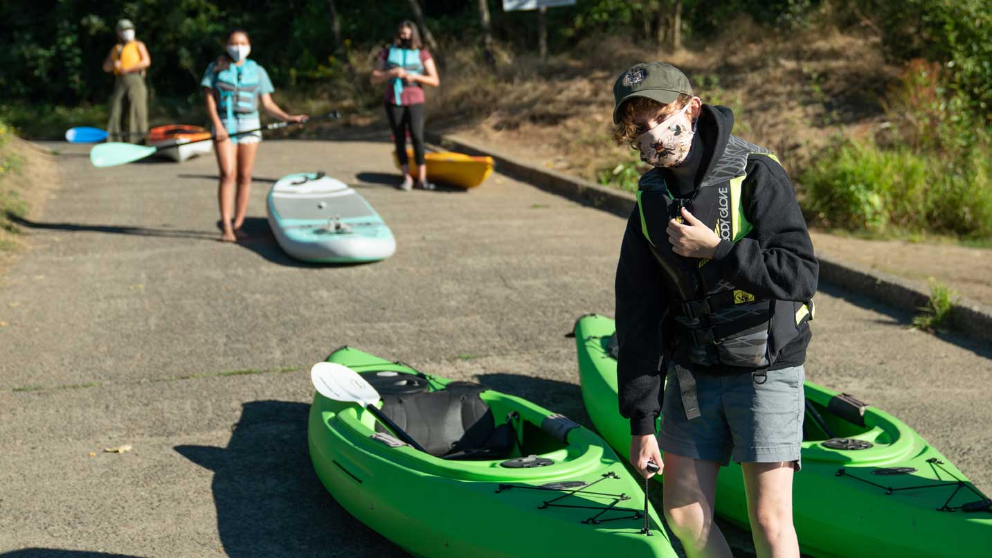 Four masked people get ready to kayak at a boat ramp.