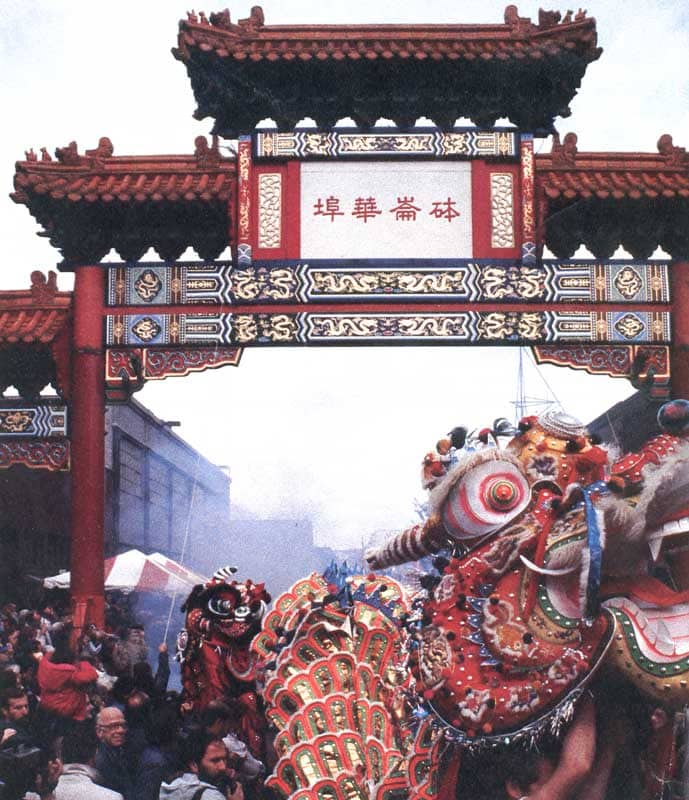 A parade of dragon dancers in front of the Chinatown Gate.