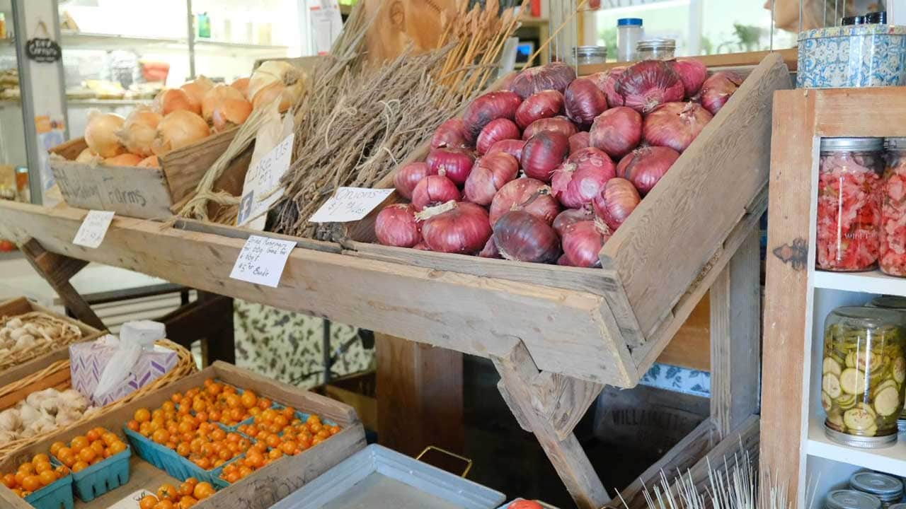 Farm stand features fresh onions and tomatoes.