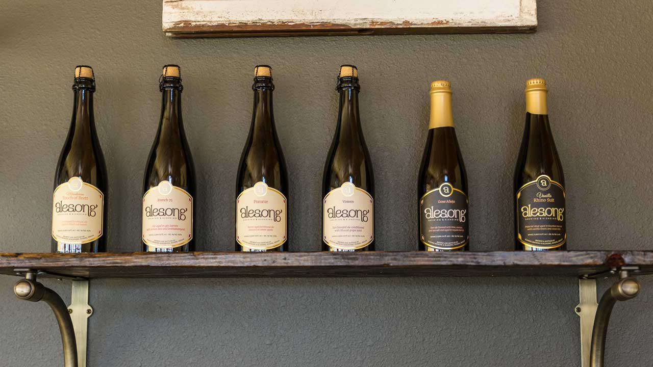 Six bottles of Alesong beer on a mantle.