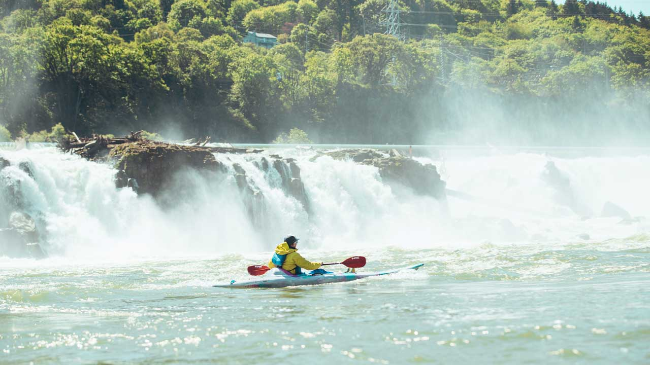 A kayaker in front of Willamette Falls