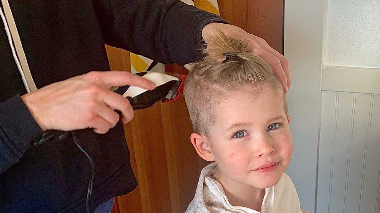 A blonde child gets a haircut.