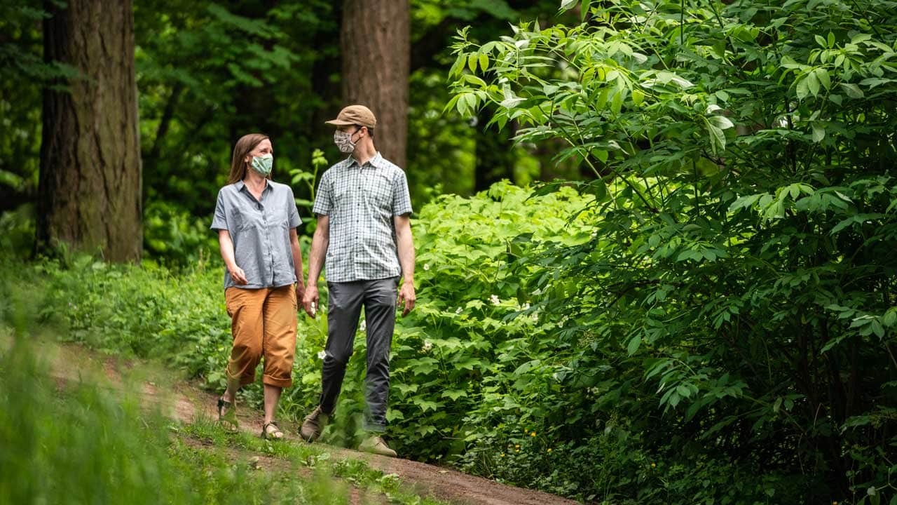 Two people wear fabric face coverings in a park.