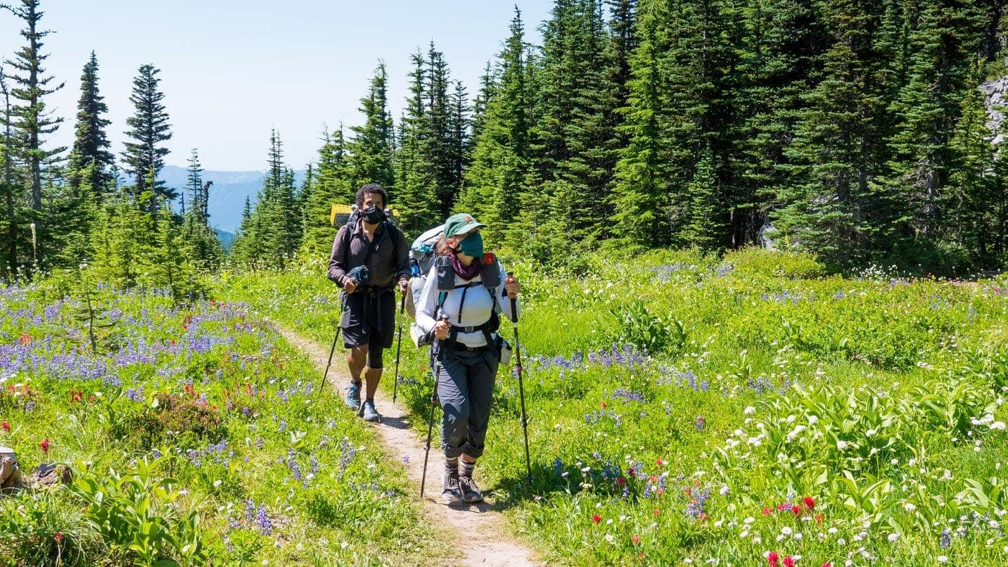 Two hikers wear face coverings while walking down a trail.