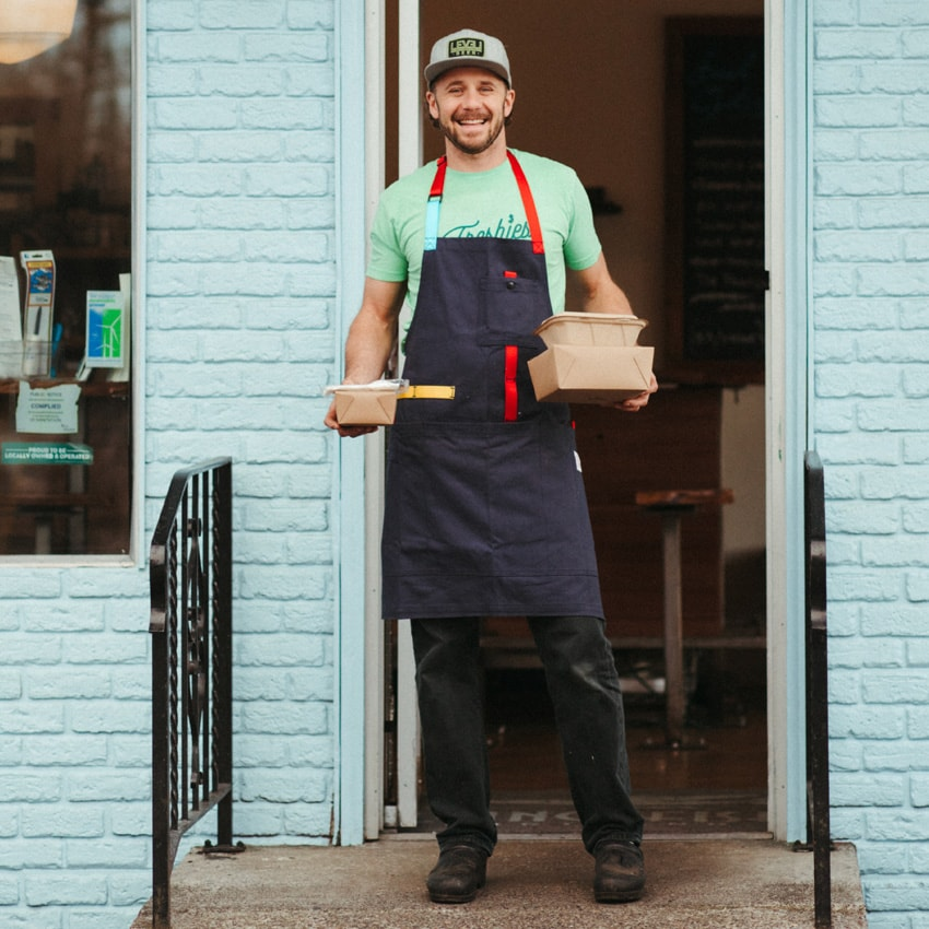 Restaurant owner Lyf Gildersleeve of Flying Fish in an apron and holding to-go containers
