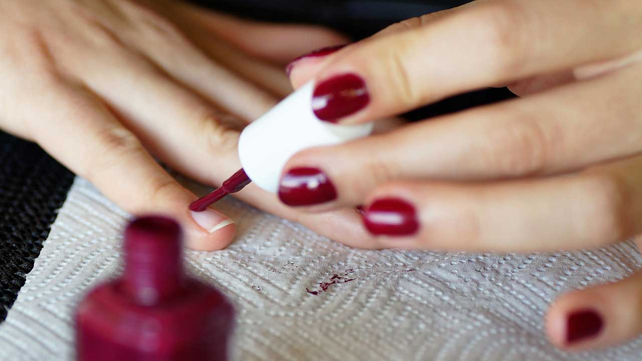 A person paints their nails red.