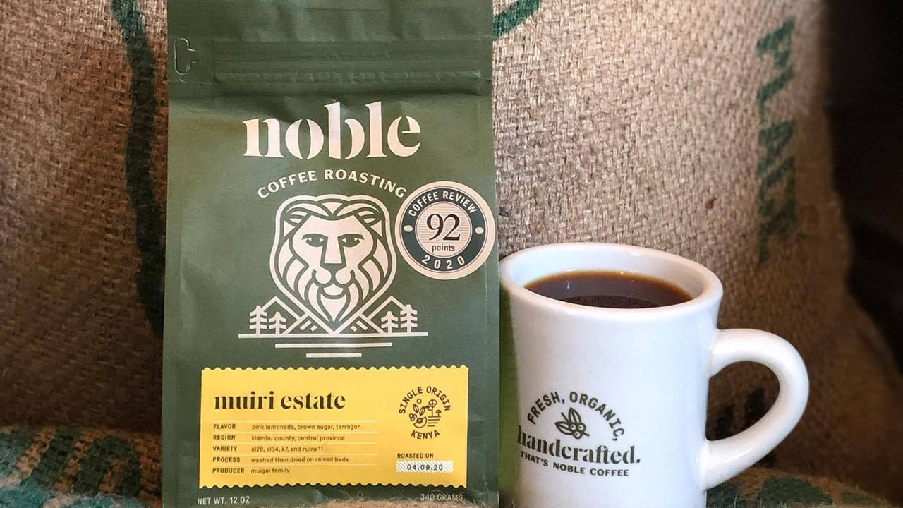 A branded Noble Coffee Roasting mug and bag of beans.