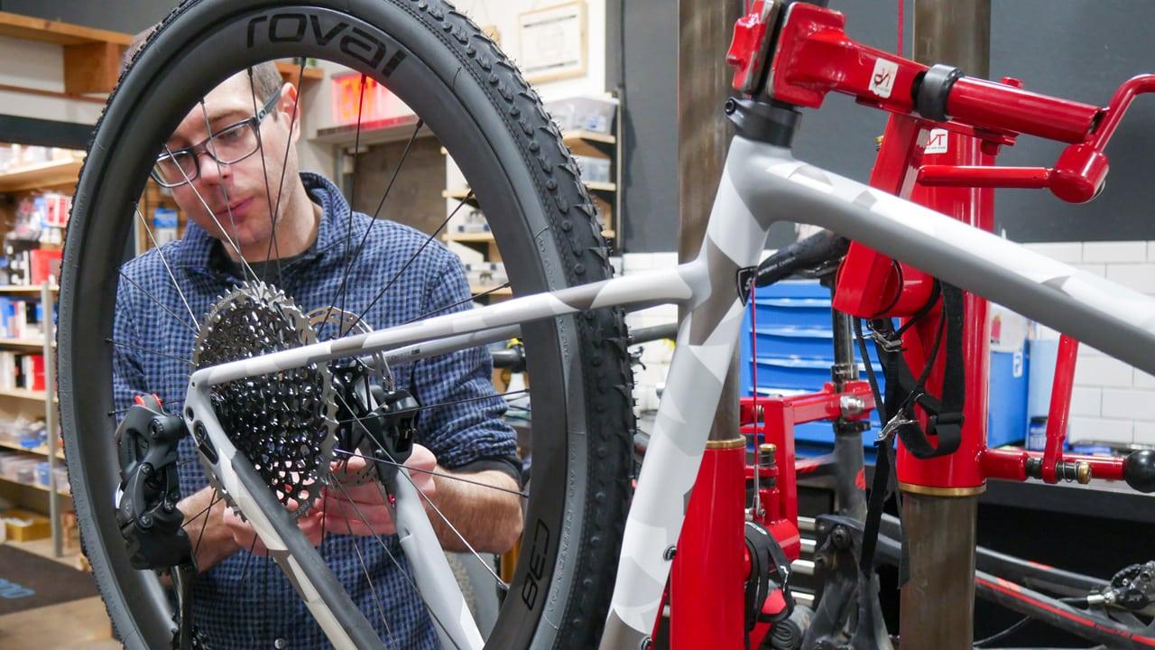 A bike mechanic examines the gears of a wheel.