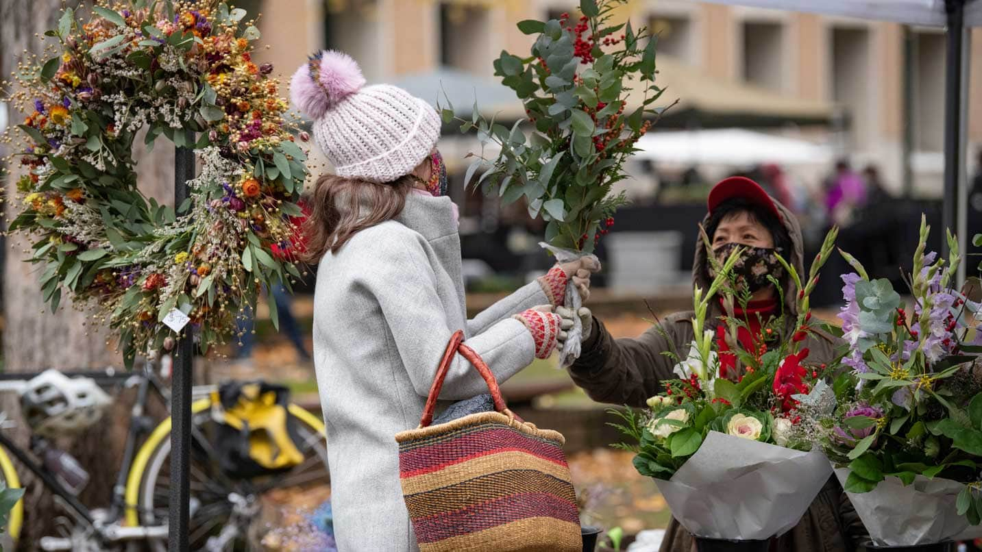 A masked florist passes a bouquet to a masked customer.