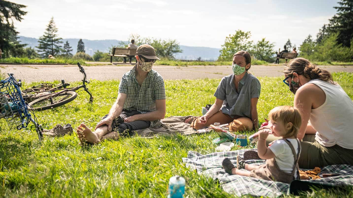 Three adults wear face coverings at a picnic while a toddler does not.