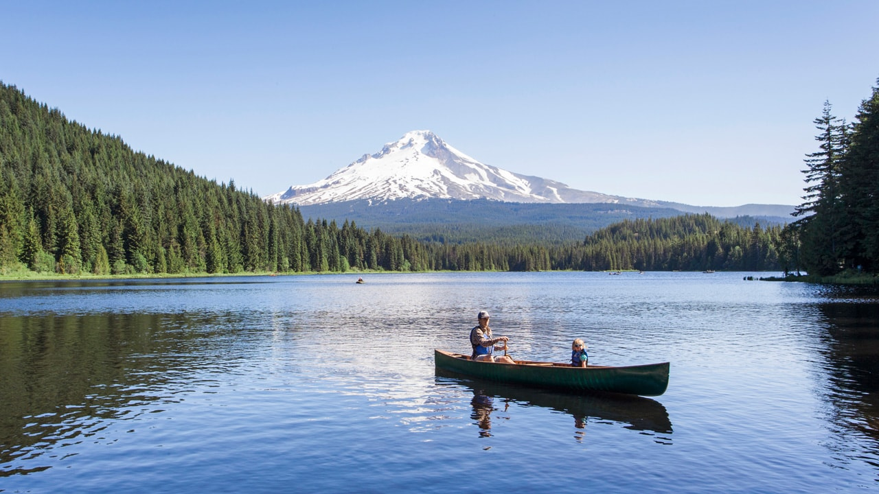 A parent and child paddle on a glassy lake.