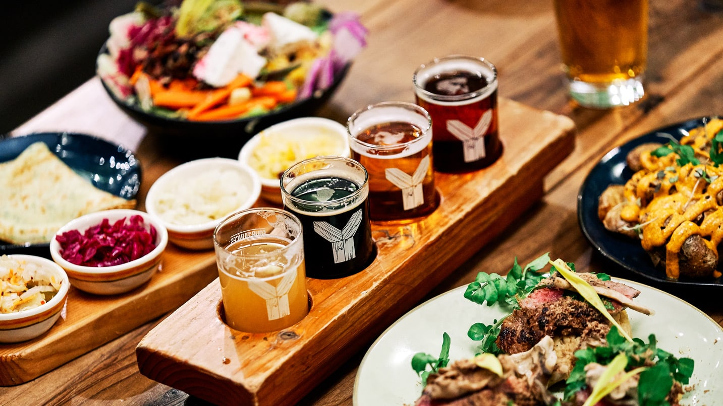 A tasting tray of beer surrounding by vegetable-heavy plates of food.
