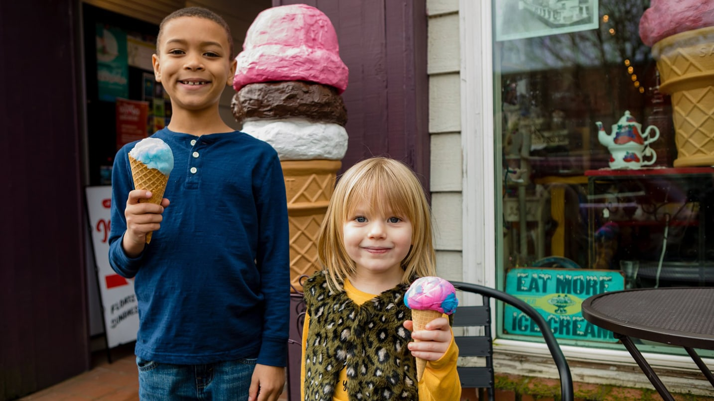 Two kids smile holding ice cream cones.