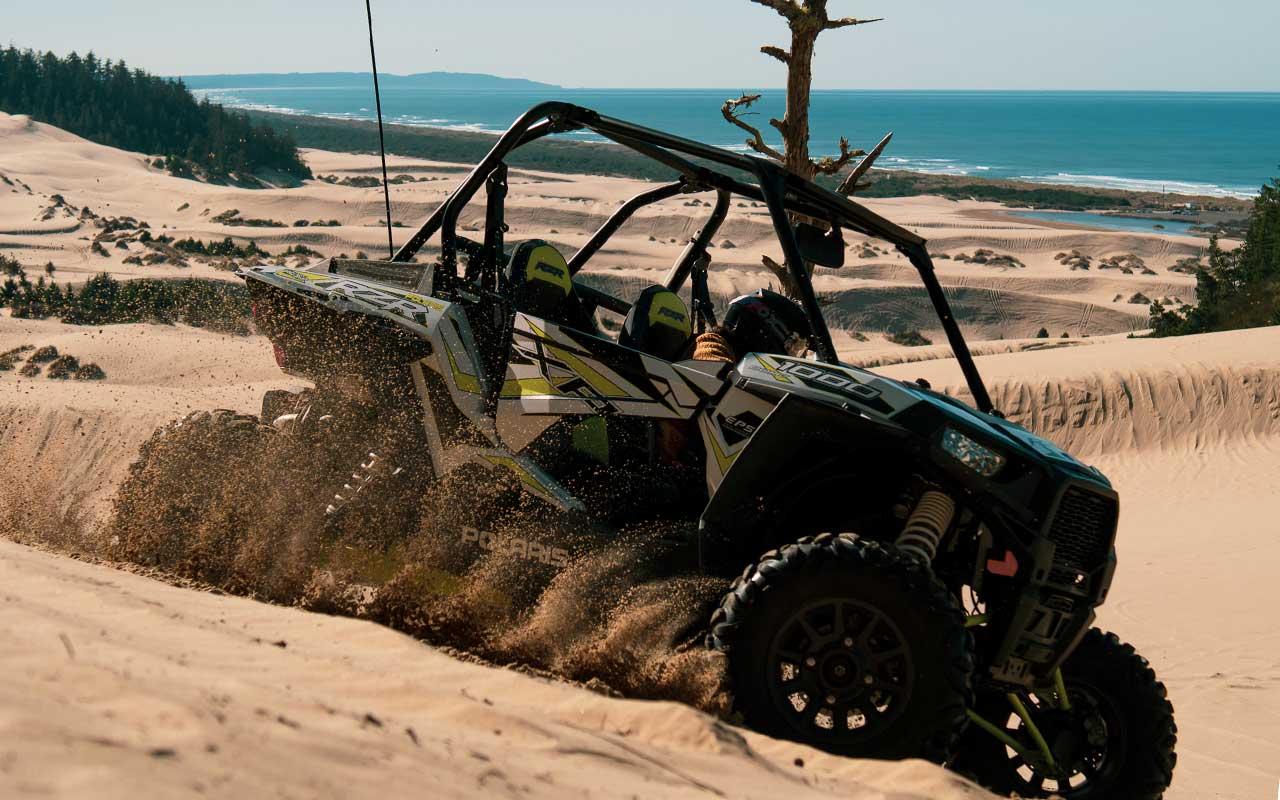 A RZR slides down a sandy dune.