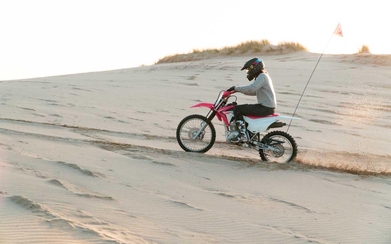 Kayla rides a motorbike up a sand dune.